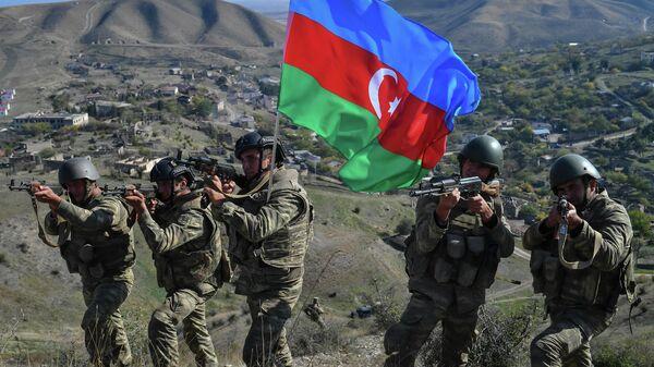 Военнослужащие азербайджанской армии во время реконструкции водружения государственного флага на господствующей высоте у села Талыш