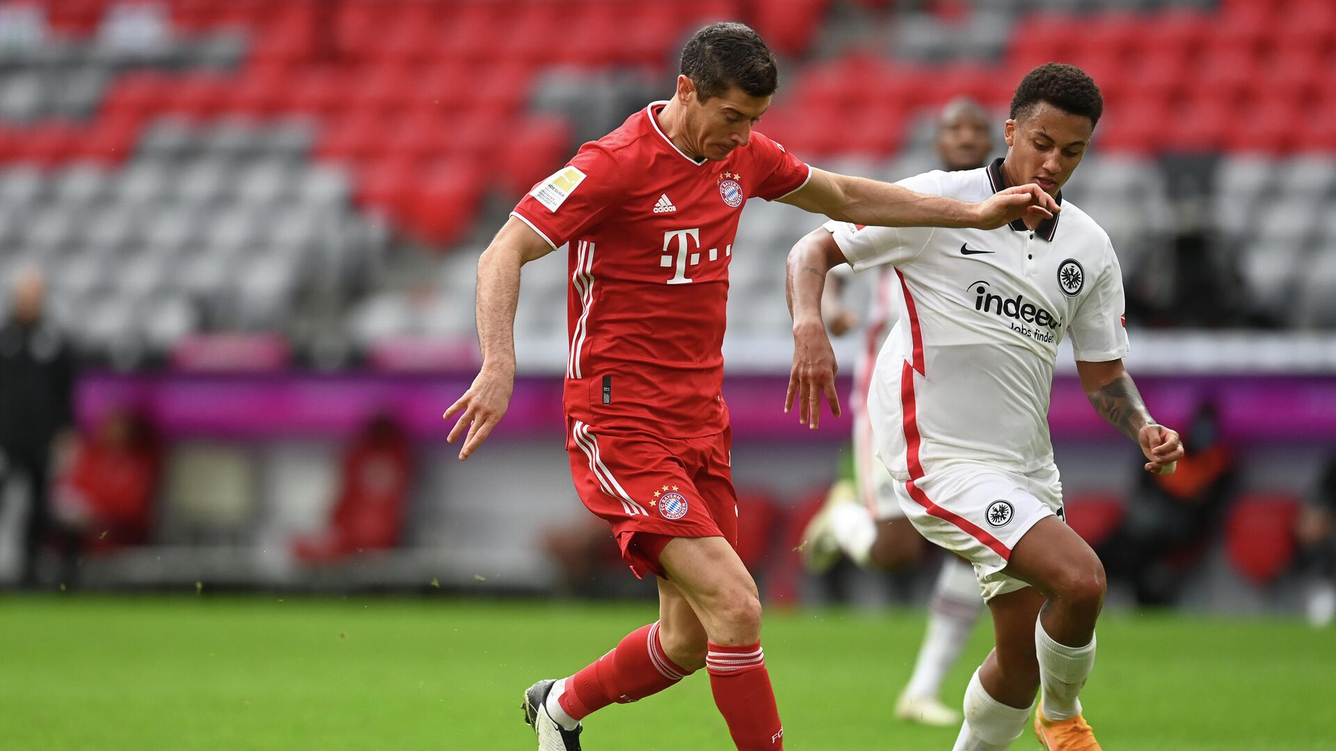Bayern Munich's Polish forward Robert Lewandowski (L) scores the 3-0 goal for his hat-trick past Frankfurt's Brazilian defender Tuta during the German first division Bundesliga football match between FC Bayern Munich and Eintracht Frankfurt on October 24, 2020 in Munich, southern Germany. (Photo by CHRISTOF STACHE / various sources / AFP) / DFL REGULATIONS PROHIBIT ANY USE OF PHOTOGRAPHS AS IMAGE SEQUENCES AND/OR QUASI-VIDEO - РИА Новости, 1920, 24.10.2020