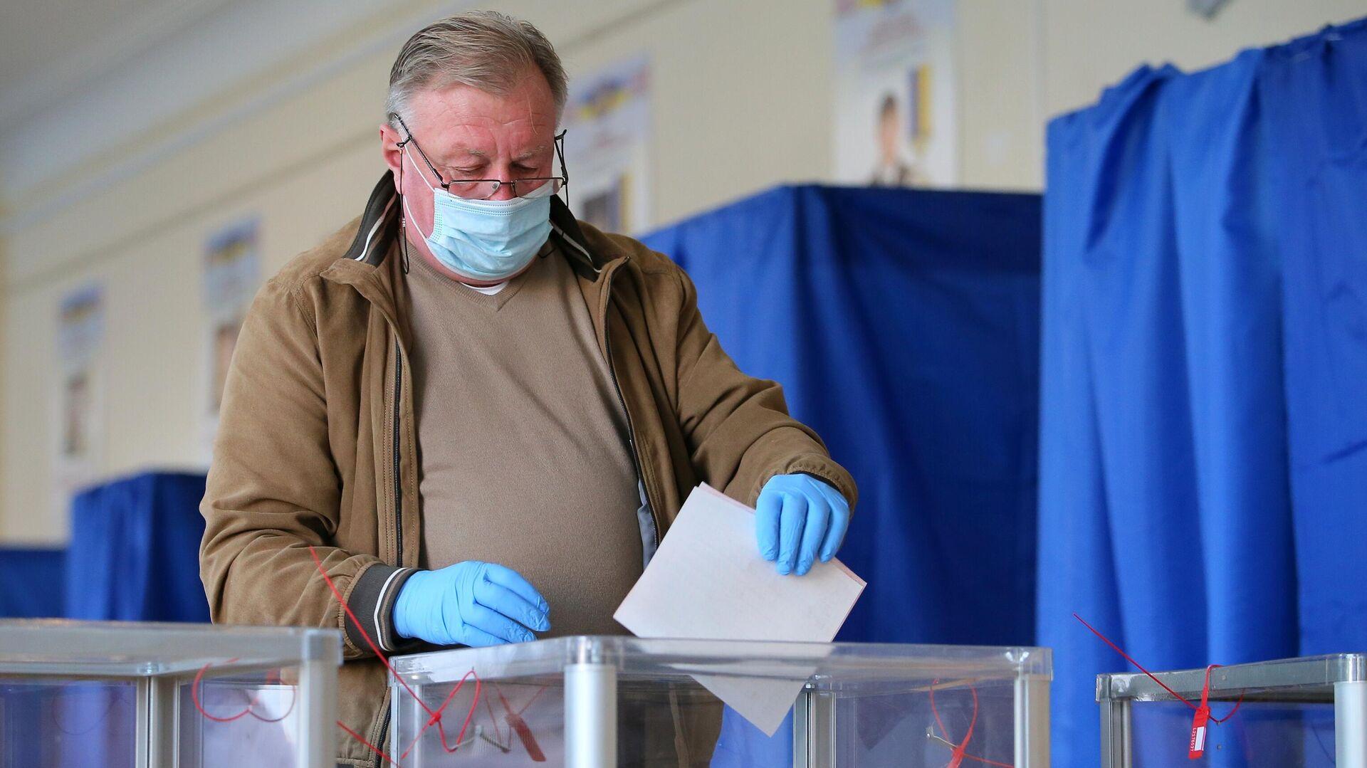 Мужчина голосует на одном из избирательных участков в Киеве - РИА Новости, 1920, 29.10.2020