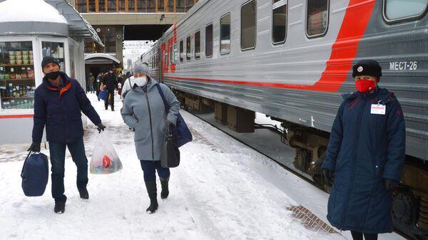 Пассажиры и проводница в защитных масках на перроне железнодорожного вокзала в Челябинске