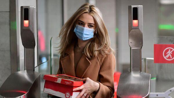 Девушка в медицинской маске проходит через турникет, с установленным дистанционным тепловизором, на станции метро Марьино Московского метрополитена