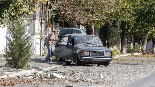 Мужчина у автомобиля, поврежденного в результате обстрелов города Мартуни в Нагорном Карабахе