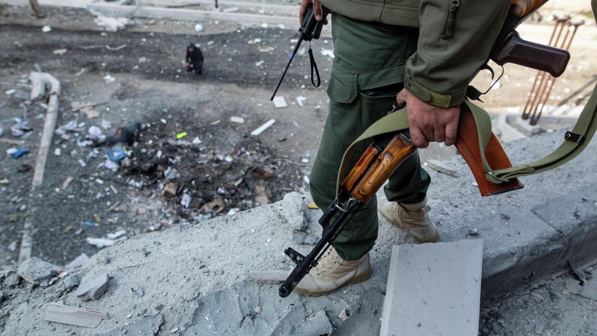 Вооруженный человек на месте удара по зданию родильного дома в Степанакерте - РИА Новости, 1920, 31.10.2020