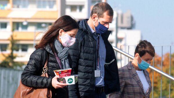 Прохожие на улице в медицинских масках