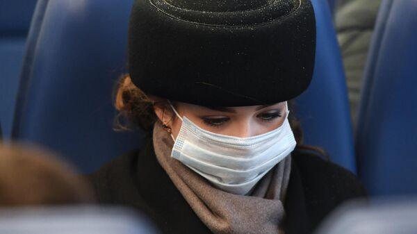 Девушка в медицинской маске в пригородном электропоезде в Новосибирске