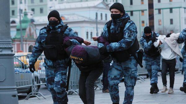 Сотрудники полиции задерживают участника акции протеста около посольства Франции в Москве