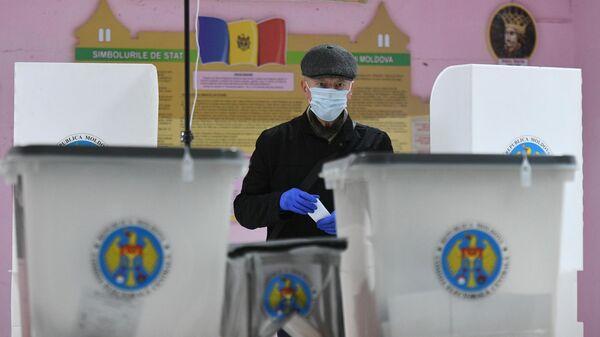 Мужчина голосует на всеобщих выборах президента Молдавии на одном из участков в Кишиневе