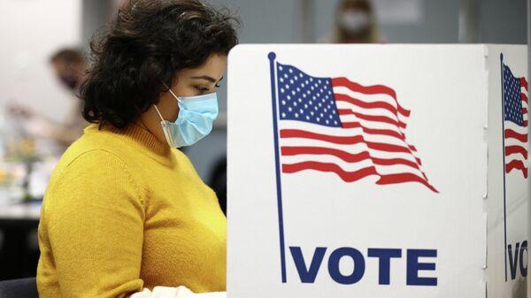Женщина голосует на выборах президента США в Фэрфаксе, штат Виргиния