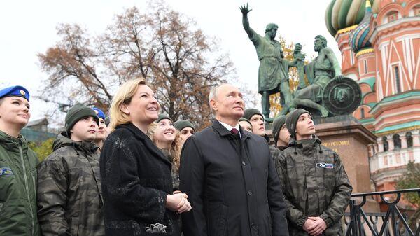 Владимир Путин вместе с представителями молодежных организаций слушают обновленный звон колоколов на Спасской башне Кремля