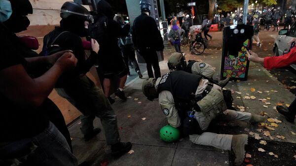 Полицейские задерживают протестующего в Портленде, штат Орегон, США