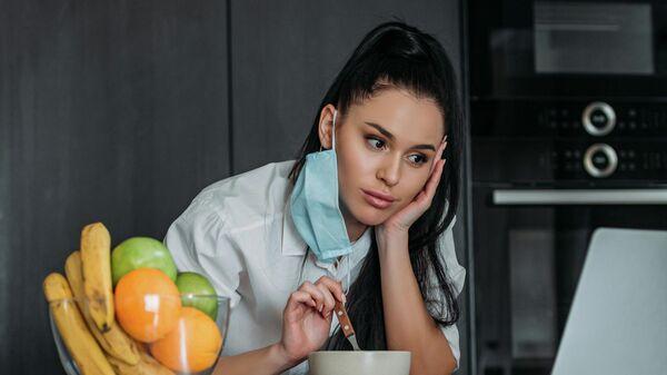 Девушка ест перед экраном ноутбука