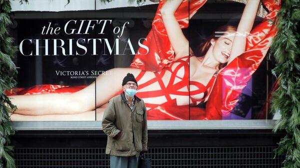 Мужчина перед рекламой закрытого магазина в Лондоне