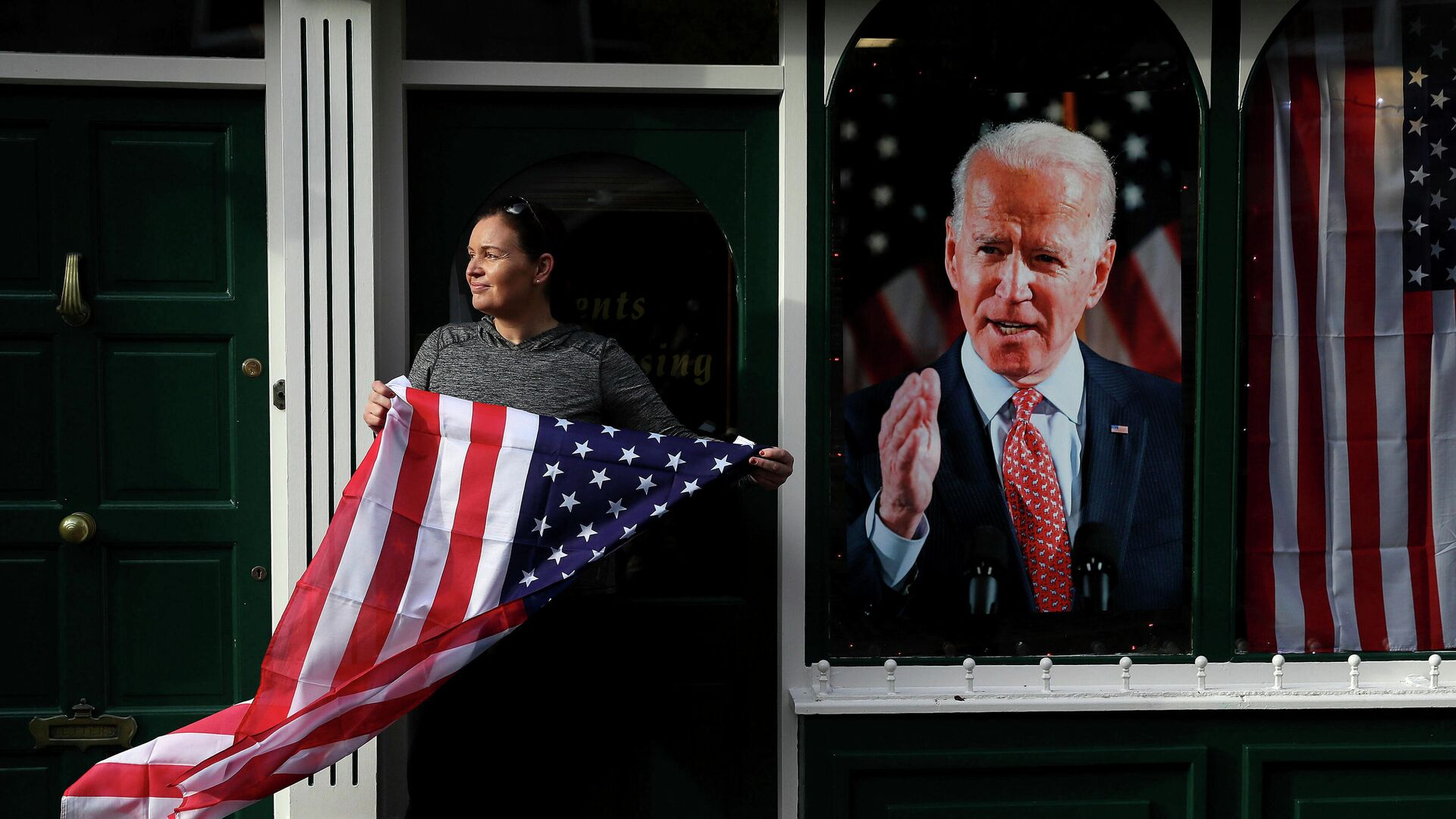 Сторонница Джо Байдена с флагом США на улице города Баллина, Ирландия - РИА Новости, 1920, 07.11.2020