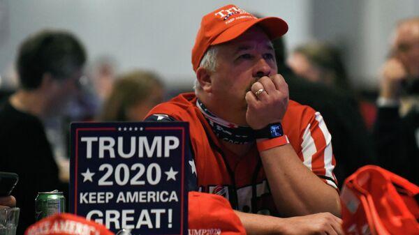 Сторонник президента США Дональда Трампа наблюдает за ходом выборов в США