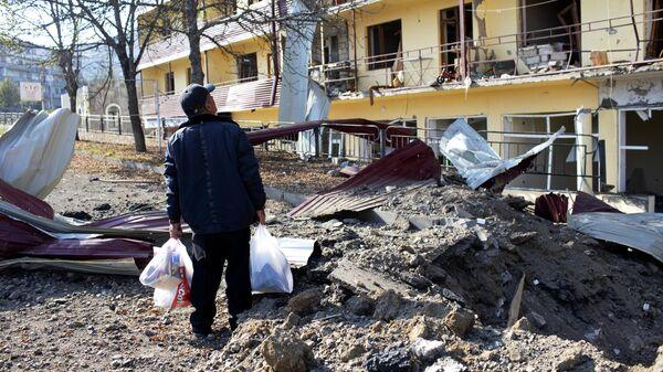 Мужчина возле дома, пострадавшего в результате обстрела города Шуша