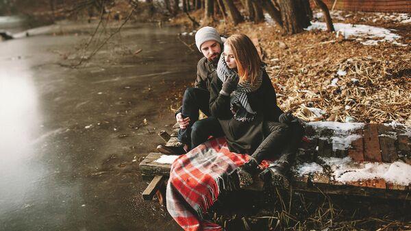 Молодая пара сидит на старом пирсе у замерзшего озера
