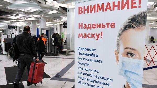 Плакат с надписью Внимание! Наденьте маску! в международном аэропорту Толмачёво в Новосибирске
