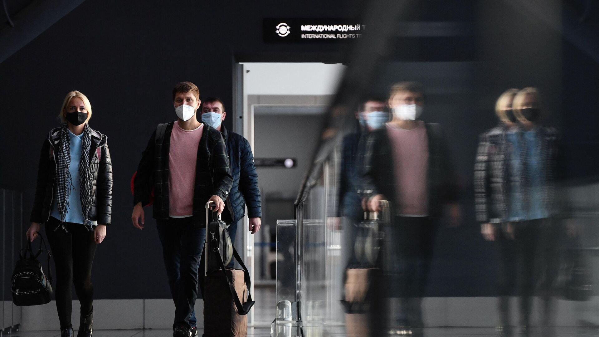 Пассажиры в защитных масках в международном аэропорту Толмачёво в Новосибирске - РИА Новости, 1920, 17.02.2021