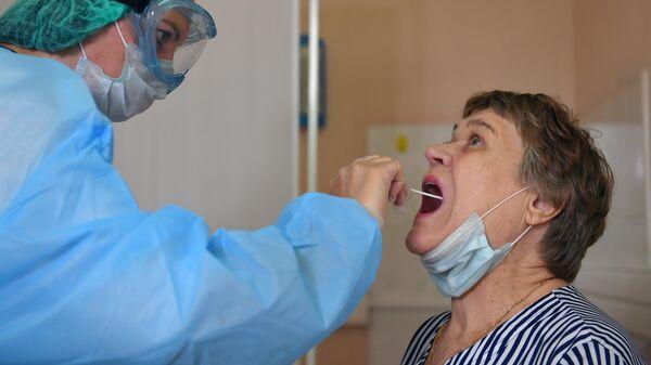 Москвичи с 1Пациентка во время взятия мазка на коронавирус COVID-19