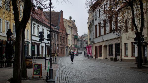 Местный житель в маске гуляет по пустому Старому городу в Вильнюсе