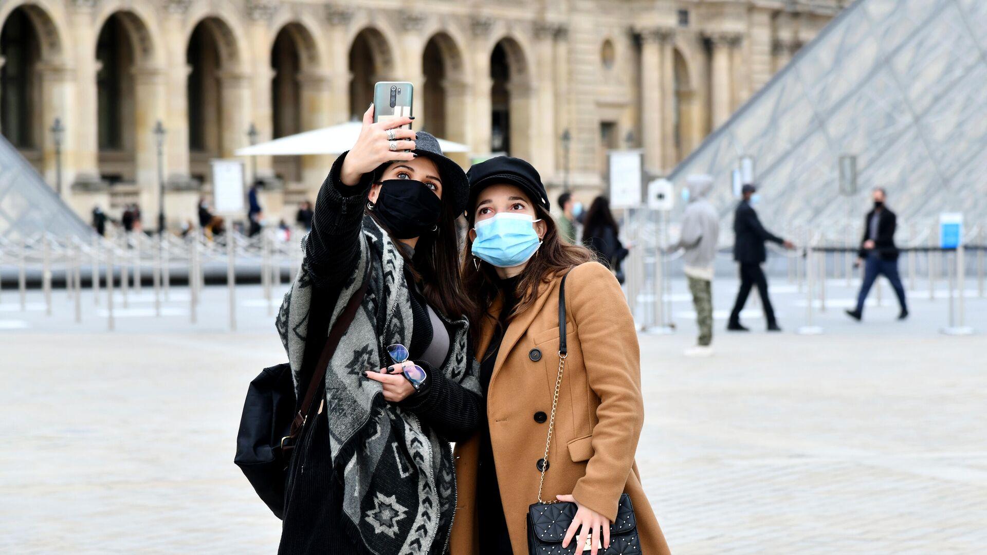 Девушки в масках фотографируются на площади у входа в музей Лувр в Париже - РИА Новости, 1920, 11.01.2021