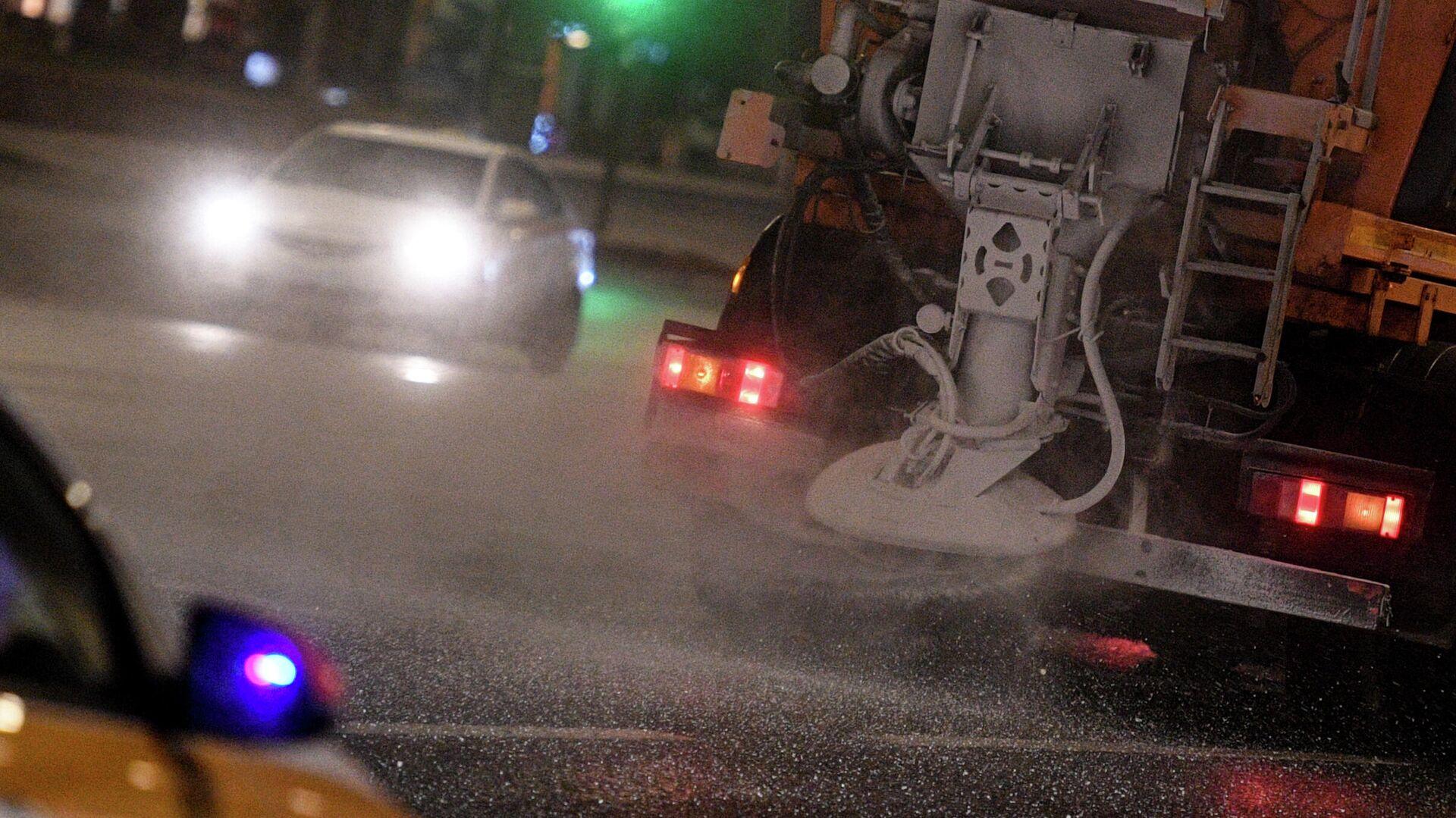 Снегоуборочная машина обрабатывает проезжую часть дороги противогололёдным средством в Москве - РИА Новости, 1920, 26.11.2020