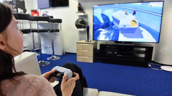 Девушка тестирует новую игровую приставку Sony PlayStation 5 в магазине в Москве