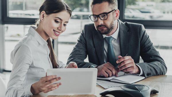 Мужчина и женщина смотрят на экран планшета