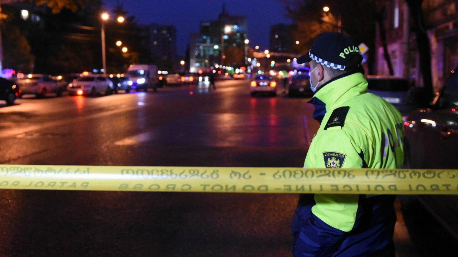 Сотрудник полиции на проспекте Церетели в Тбилиси, где вооруженный мужчина, который ворвался в офис микрофинансовой организации, удерживает в заложниках девять человек - РИА Новости, 1920, 20.11.2020
