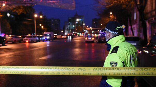 Сотрудник полиции на проспекте Церетели в Тбилиси, где вооруженный мужчина, который ворвался в офис микрофинансовой организации, удерживает в заложниках девять человек