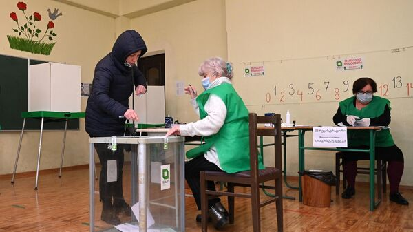 Женщина голосует во время второго тура парламентских выборов на избирательном участке в Тбилиси