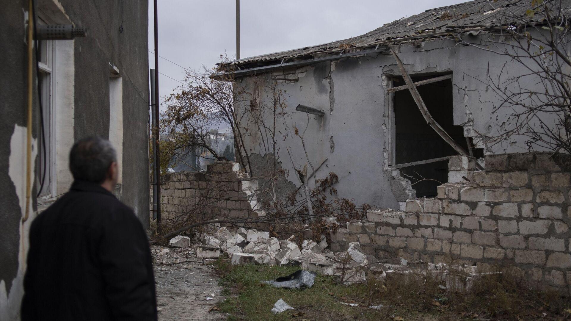 Мужчина возле частично разрушенного дома в Мартакерте - РИА Новости, 1920, 23.11.2020