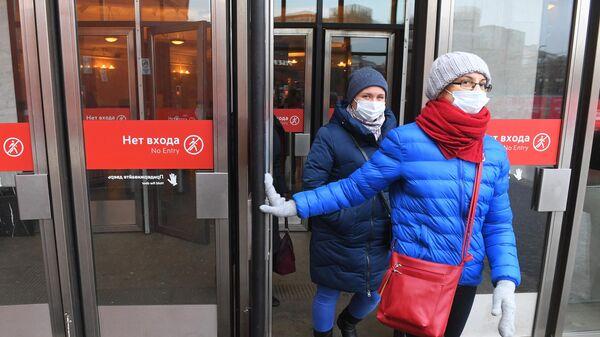 Девушки в защитных масках выходят у станции Московского метрополитена.