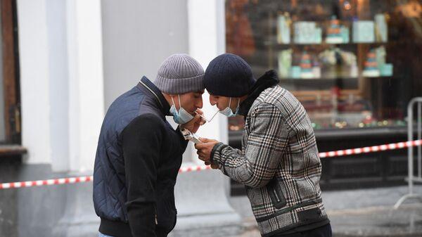 Мужчины в защитных масках на одной из улиц в Москве