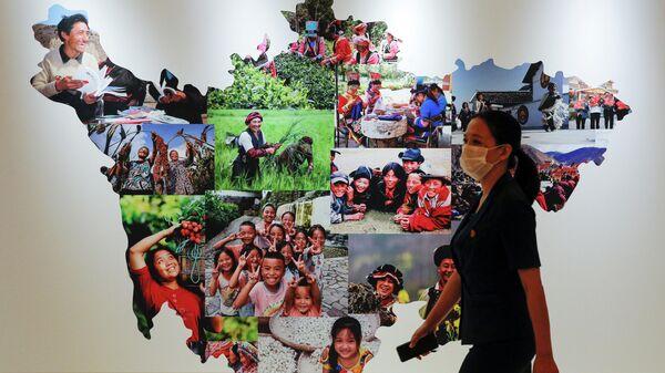 Женщина в защитной маске проходит мимо карты провинции Сычуань