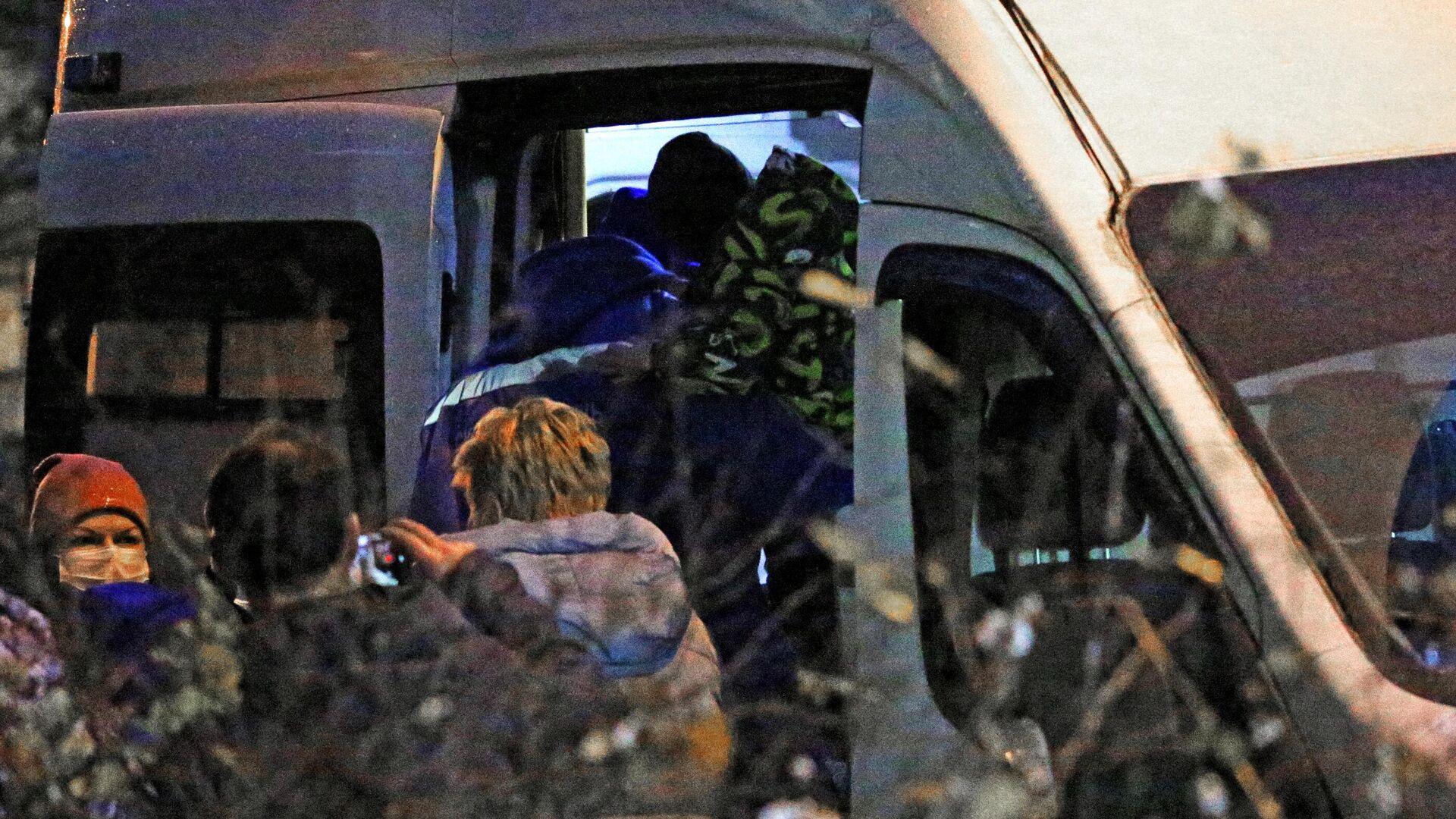 Сотрудник скорой помощи заносит в автомобиль одного из шестерых детей, освобожденных после захвата в городе Колпино - РИА Новости, 1920, 24.11.2020