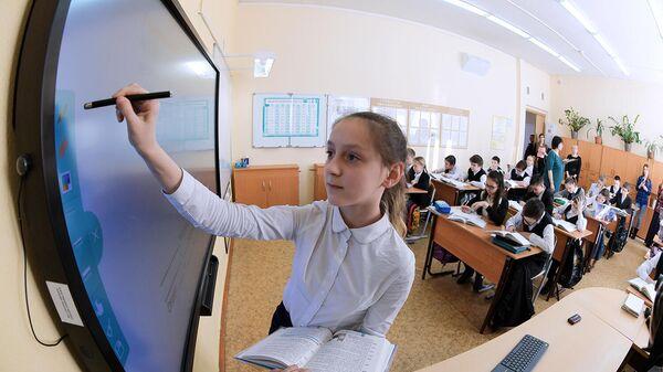 Ученица выполняет задание возле интерактивной доски