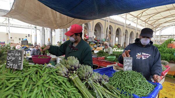 Продавцы в защитных масках на центральном рынке в Тунисе