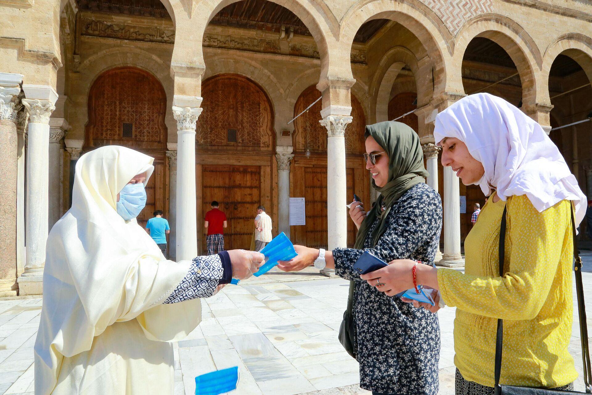 Женщина раздает защитные маски возле мечети аз-Зайтуна в Тунисе - РИА Новости, 1920, 25.11.2020