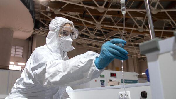 Медицинский работник ставит капельницу пациенту во временном госпитале для пациентов с COVID-19, развернутом в ледовом дворце Крылатское