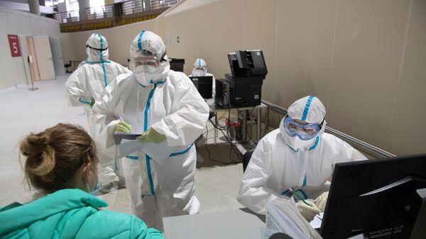 Медицинский работники приемного отделения осматривает пациентку во временном госпитале для пациентов с COVID-19, развернутом в ледовом дворце Крылатское