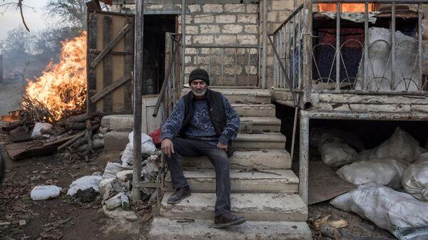 Мужчина сидит на крыльце горящего дома в поселке Карегах в Нагорном Карабахе