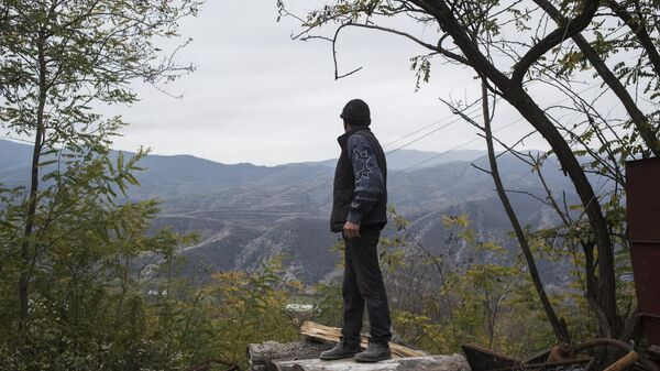 Мужчина смотрит на горы возле своего дома в поселке Карегах
