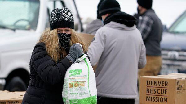 Волонтер с замороженной индейкой во время раздачи еды в рамках акции Банкет в коробке