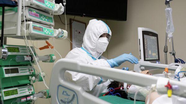 Медицинский работник и пациент в отделении реанимации и интенсивной терапии в госпитале COVID-19 в городской клинической больнице № 52 в Москве