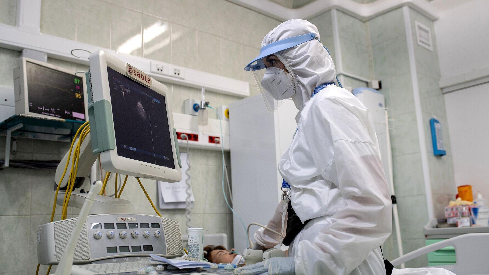 Врач делает УЗИ пациенту в отделении реанимации и интенсивной терапии в госпитале COVID-19 в городской клинической больнице № 52 в Москве. - РИА Новости, 1920, 04.12.2020