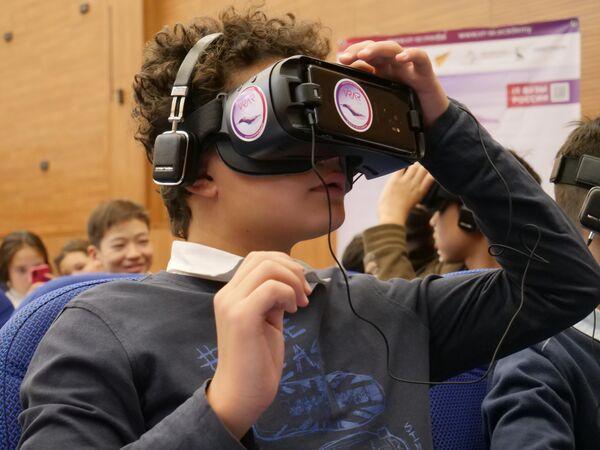 Киргизский школьник совершает виртуальный выход на поверхность спутника Земли в ходе  презентации VR-проекта Лунная станция