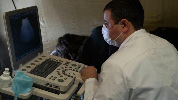 Врач и пациентка во время процедуры в кабинете УЗИ на базе полевого госпиталя развернутого Министерством обороны России на территории аэропорта в Степанакерте
