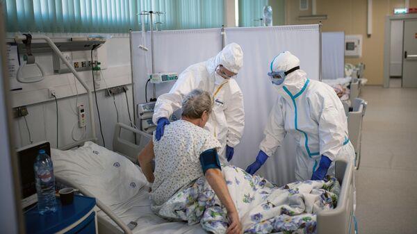 Медицинские работники и пациент в отделении реанимации и интенсивной терапии в госпитале для больных COVID-19