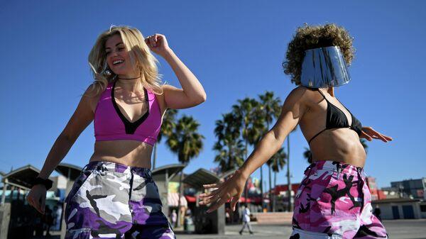 Девушка катаются на роликах по пляжу в Лос-Анджелесе, штат Калифорния, США